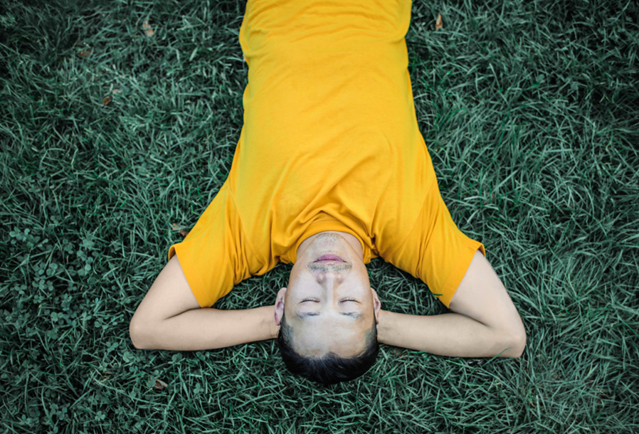 A man relaxes, laying on the grass with his eyes closed