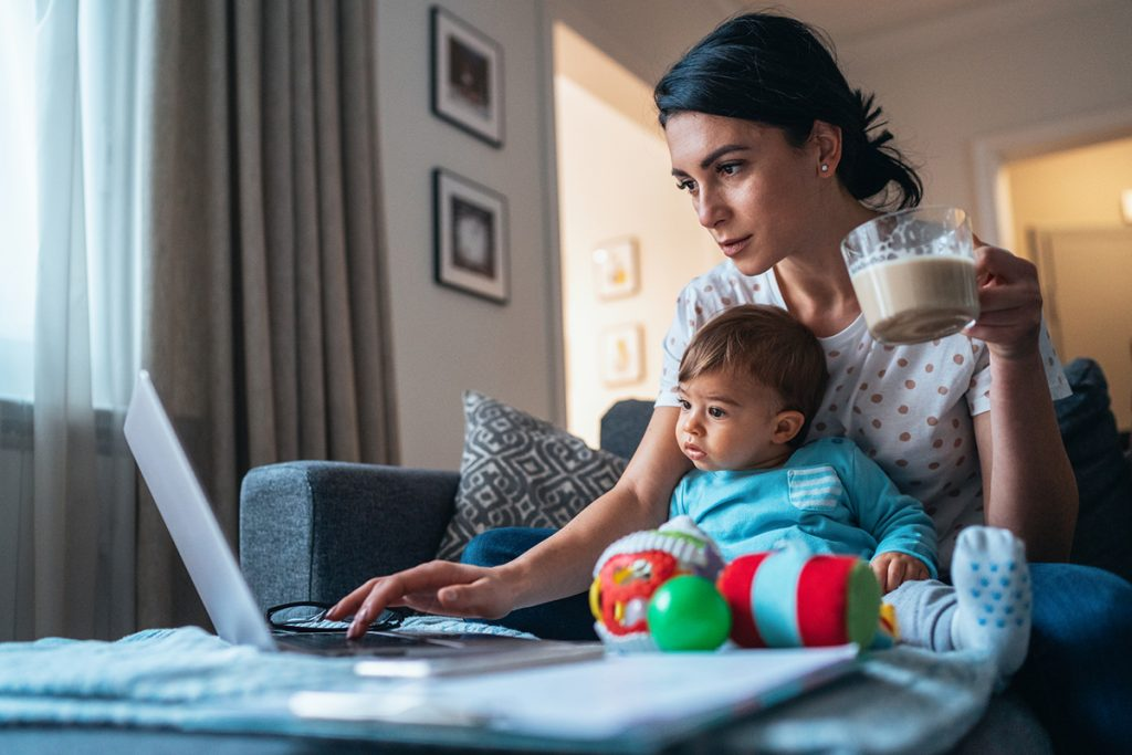 Young mother with a baby using laptop at home