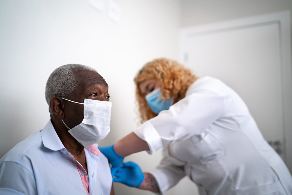 An older gentleman receives a vaccination from a healthcare professional