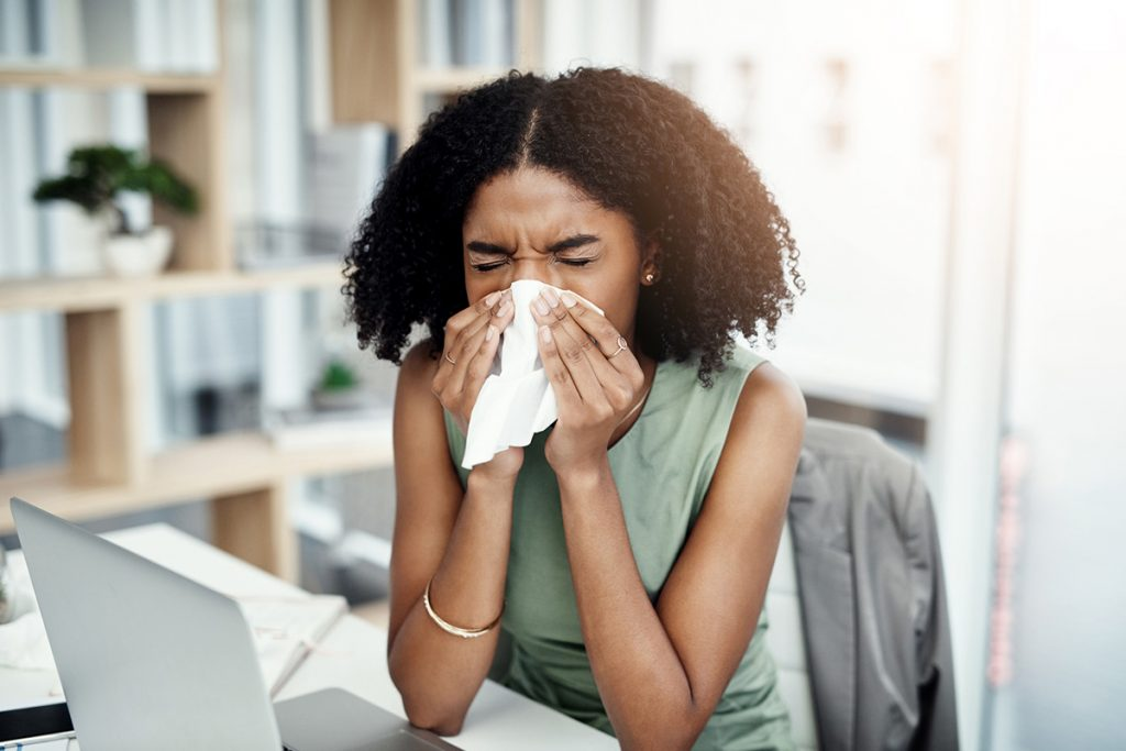 A young businesswoman blowing her nose while sitting at her desk in the office